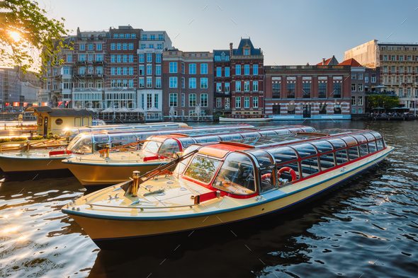 Tourist boats moored in Amsterdam canal pier on sunset - Stock Photo - Images