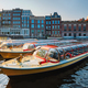Tourist boats moored in Amsterdam canal pier on sunset - PhotoDune Item for Sale