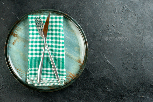 top view crossed steel dinner knife and fork on green and white checkered napkin on platter on - Stock Photo - Images