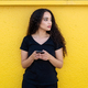 Young black woman with long hair and black outfit with a phone standing In Front Of A Yellow Wall - PhotoDune Item for Sale