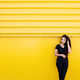 Stylish young black woman with long hair in black outfit in front of a vibrant yellow background - PhotoDune Item for Sale
