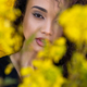 Exotic woman standing behind yellow blooming flowers - PhotoDune Item for Sale