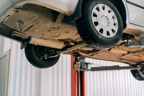 Car lifted on car lift for routine maintenance - Stock Photo - Images