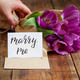 Hand with Bouquet and MARRY ME card on wooden table - PhotoDune Item for Sale