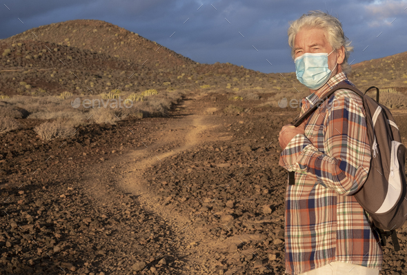 Elderly man walking in a path in an arid landscape enjoying nature. Cloudy sky and mountains - Stock Photo - Images