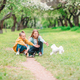 Little smiling girls playing and hugging puppy in the park - PhotoDune Item for Sale