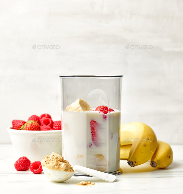 fresh banana, berries and milk in blender container - Stock Photo - Images