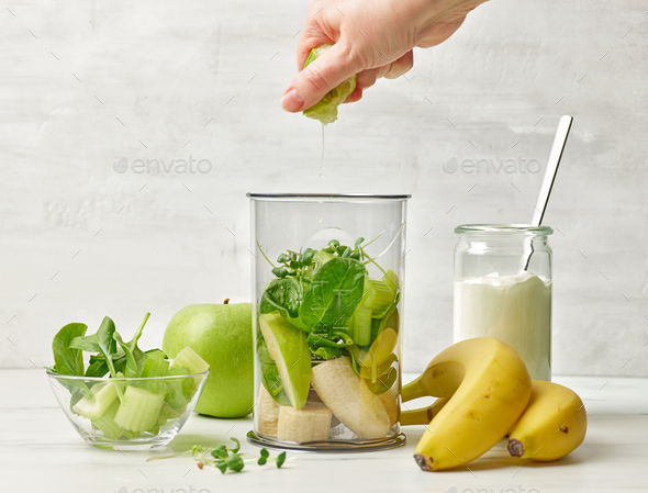 banana and various green vegetables in blender container - Stock Photo - Images