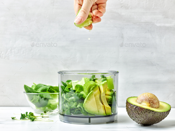 cook squeezing lime into blender container - Stock Photo - Images