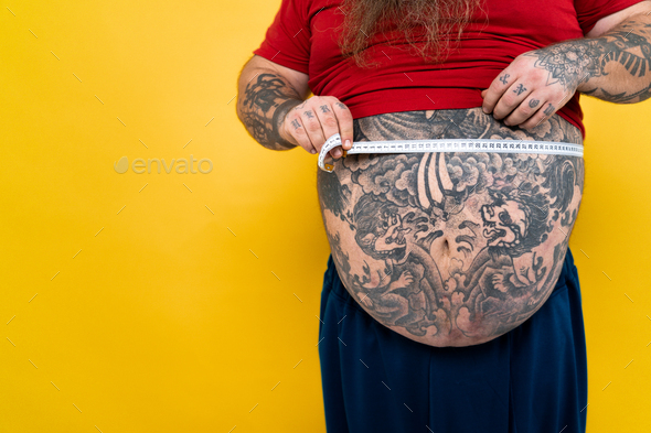 Oversize man hungry for fat food - Stock Photo - Images