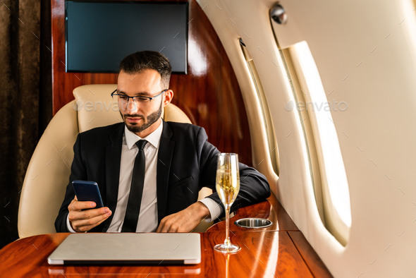 Businessman flying on private jet - Stock Photo - Images