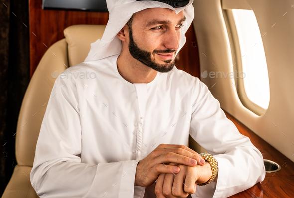 Arabian man wearing kandora flying on private jet - Stock Photo - Images