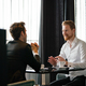 Successful businessman smiling while discussing with partner during meeting at coffee break - PhotoDune Item for Sale