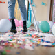 Woman with pushbroom cleaning mess of floor in room after party confetti - PhotoDune Item for Sale
