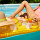 Little girl relaxing in swimming pool, enjoying suntans, drink a juice on inflatable yellow mattress - PhotoDune Item for Sale