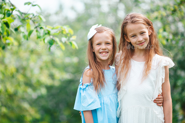 Adorable little girls in blooming apple tree garden on spring day - Stock Photo - Images