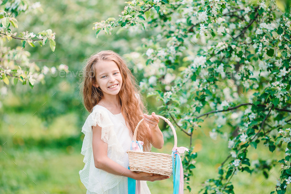 Adorable little girl in blooming apple garden on beautiful spring day - Stock Photo - Images
