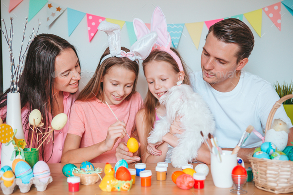 Mother and her little daughter painting eggs. Happy family preparing for Easter - Stock Photo - Images