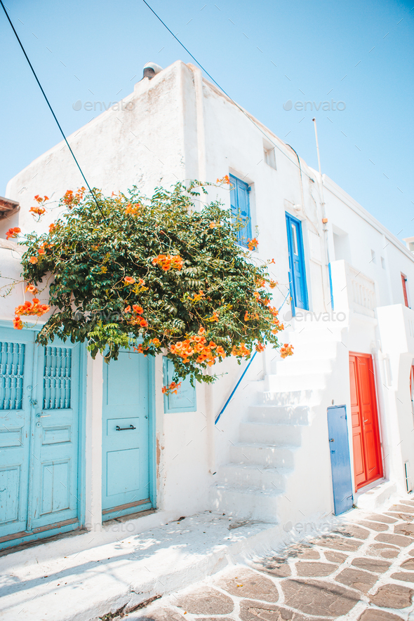 The narrow streets of the island with blue balconies, stairs and flowers in Greece - Stock Photo - Images