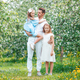 Adorable family in blooming cherry garden on beautiful spring day - PhotoDune Item for Sale