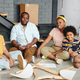 Cheerful African family of father, mother and two children sitting on the floor of large living-room - PhotoDune Item for Sale