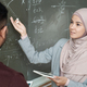 Young female student looking at professor and pointing at graph while both standing by blackboard - PhotoDune Item for Sale