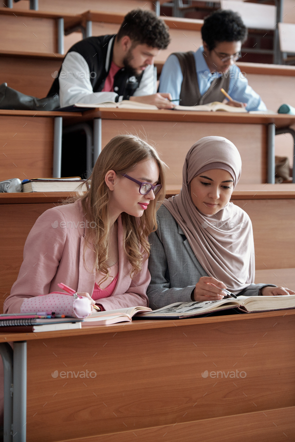Two intercultural female students of university sitting on the first row by desk in lecture hall - Stock Photo - Images