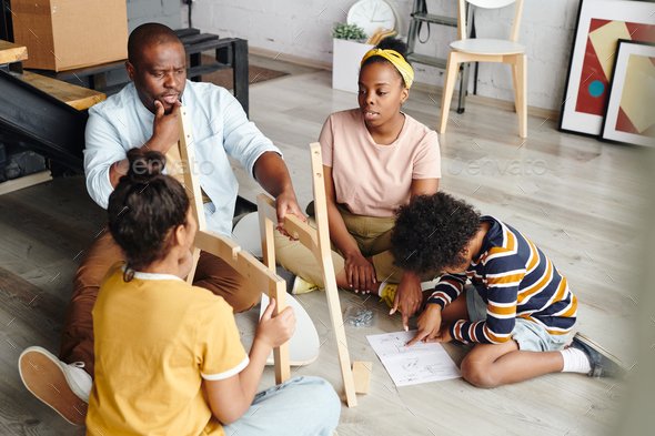 Puzzled African man looking at parts of chair while woman and boy pointing at assembling instruction - Stock Photo - Images