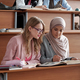 Two intercultural female students of university sitting on the first row by desk in lecture hall - PhotoDune Item for Sale