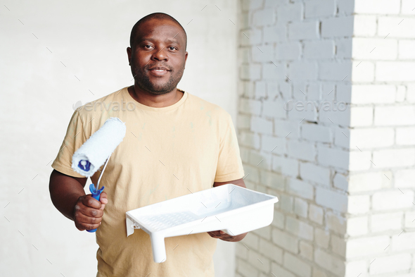 Happy African man with paintroller and white plastic container with paint standing against two walls - Stock Photo - Images