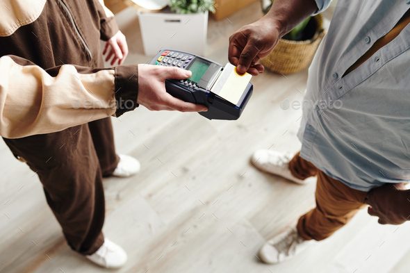 Hand of young man of African ethnicity paying for work of loaders while holding card over terminal - Stock Photo - Images