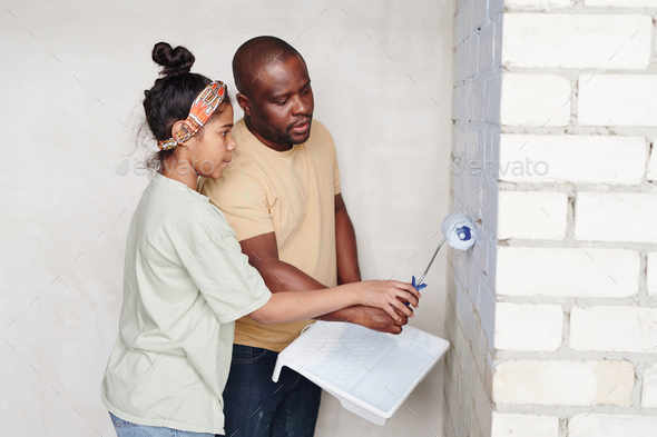 Young African man helping his cute daughter with paintroller painting brick wall of living-room - Stock Photo - Images