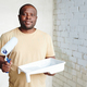 Happy African man with paintroller and white plastic container with paint standing against two walls - PhotoDune Item for Sale