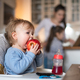 Small toddler girl sitting in highchair and eating apple - PhotoDune Item for Sale
