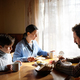 Portrait of poor sad small girl with parents eating indoors at home, poverty concept - PhotoDune Item for Sale