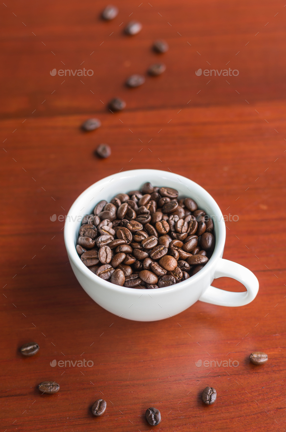 Coffee beans in coffee cup on wood with smoke and smile from coffee beans - Stock Photo - Images