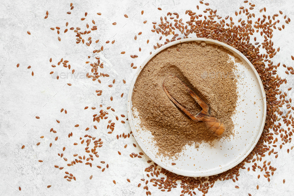 Raw Flax seeds flour in a plate with a spoon - Stock Photo - Images