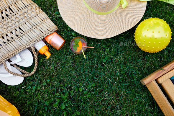Flat lay of outdoor bright summer beach vacation or travel lifestyle concept on grass background - Stock Photo - Images