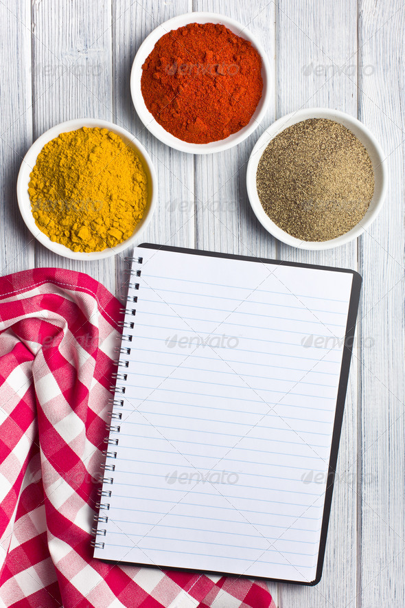 various colored spices with blank recipe book - Stock Photo - Images