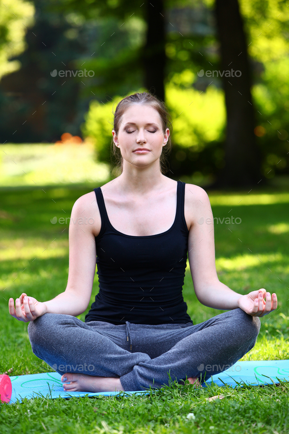 Beautiful woman relaxing in yoga pose - Stock Photo - Images