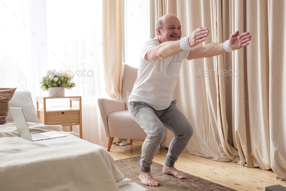 Senior man practicing yoga at home doing Chair pose, Utkatasana - Stock Photo - Images