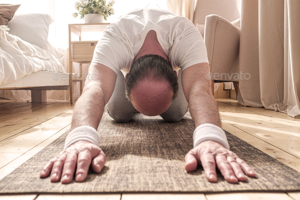 Active senior man doing the child pose while practicing yoga on a mat - Stock Photo - Images