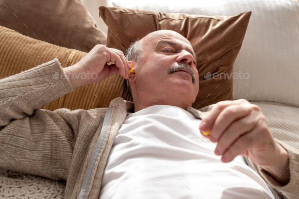 Senior stressed man holding a yellow earplug trying to sleep having insomnia - Stock Photo - Images