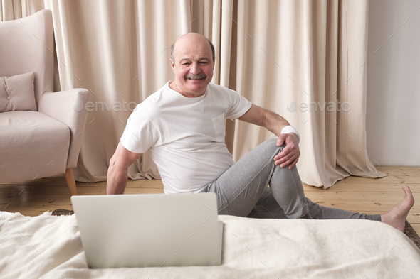 Senior caucasian man doing yoga Spine twisting pose - Stock Photo - Images