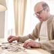 Senior caucasian man working on a puzzle - PhotoDune Item for Sale