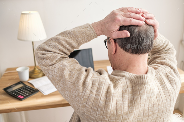 Man worried about bills holding hands on head being stressed with debts. - Stock Photo - Images