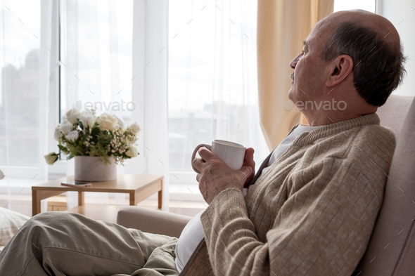 Portrait of relaxed senior man sitting on sofa with warm drink - Stock Photo - Images
