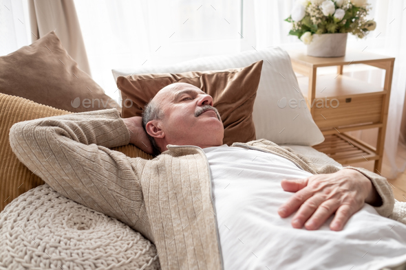 Senior man asleep in bed at home napping after breakfast - Stock Photo - Images