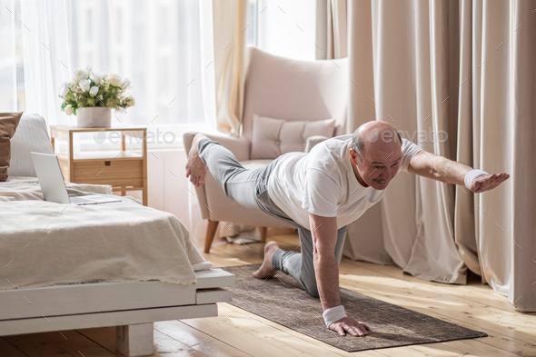 Senior caucasian men practices yoga asana chakravakasana, bird pose at home - Stock Photo - Images
