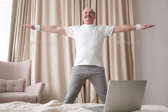 Portrait of a smiling senior man in sportswear standing at yoga asana - Stock Photo - Images
